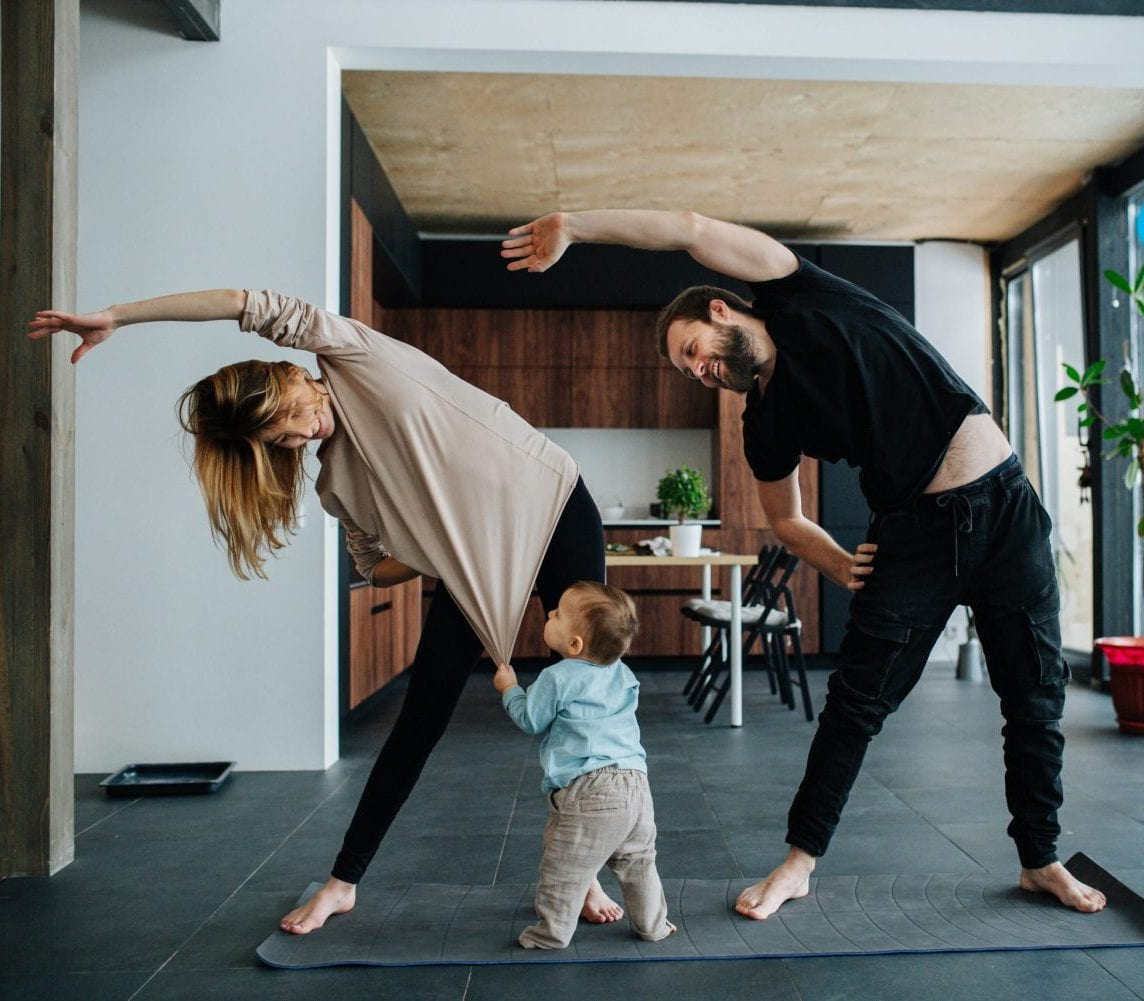 Mother and father doing morning exercises while spending time with their child